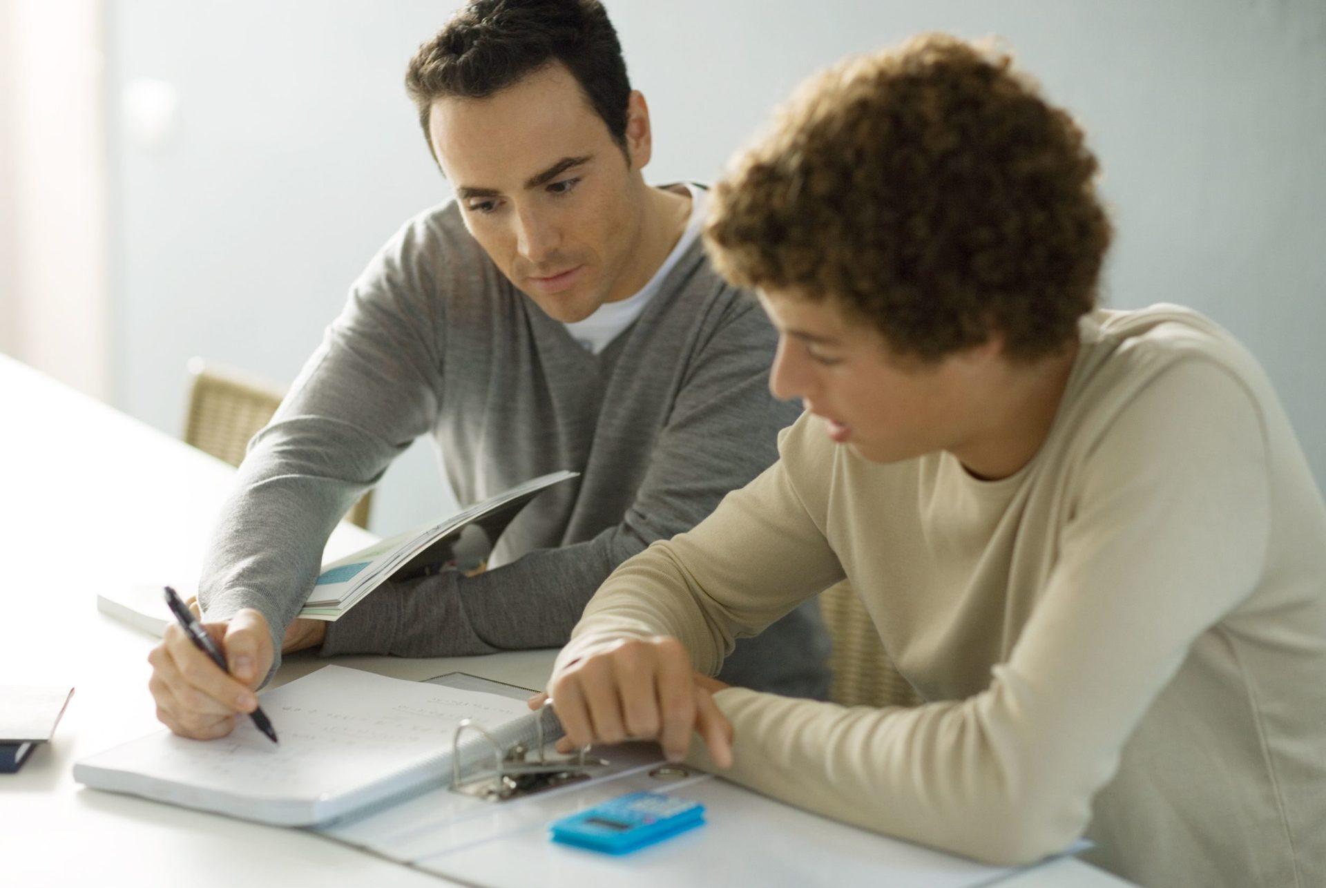 Enseignant qui aide un adolescent à faire ses devoirs